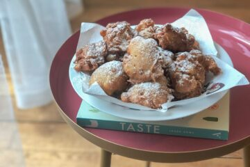 Apple fried fritters on a book on a table