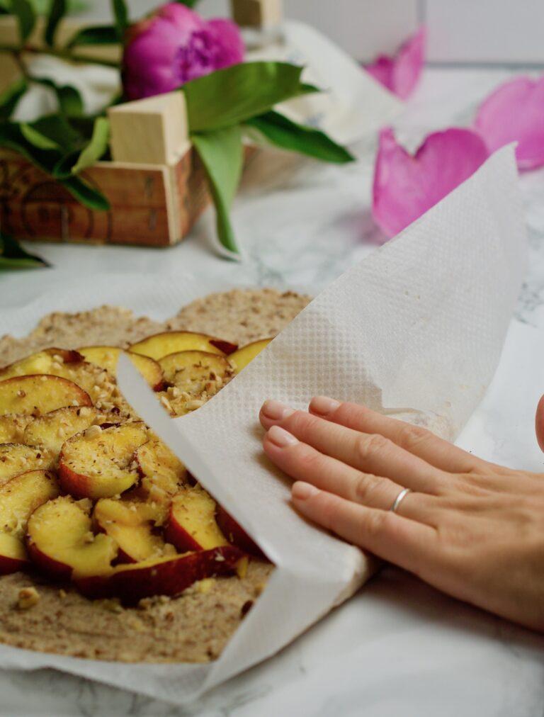 Folding a peach galette with parchment paper.