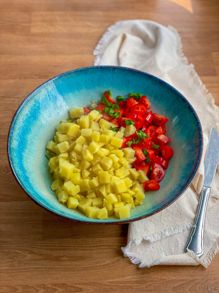Tomatoes and cubed boiled potatoes in a bowl
